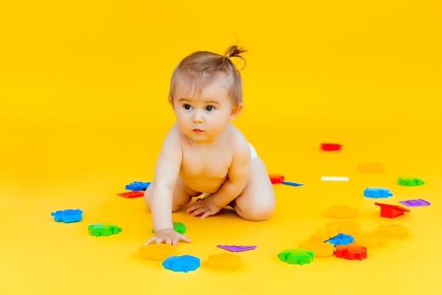 11 monate baby spielt mit spielzeug auf gelbem hintergrund. porträt eines kindes isoliert auf gelbem hintergrund