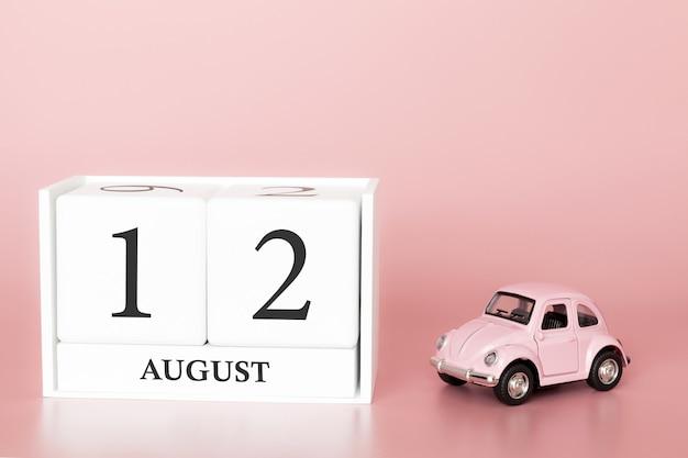 12. august tag 12 des monats, kalenderwürfel auf modernem rosa hintergrund mit auto