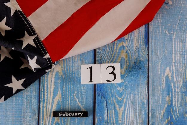 13. februar kalender wunderschön wehenden stern und gestreifte amerikanische flagge auf altem holzbrett.