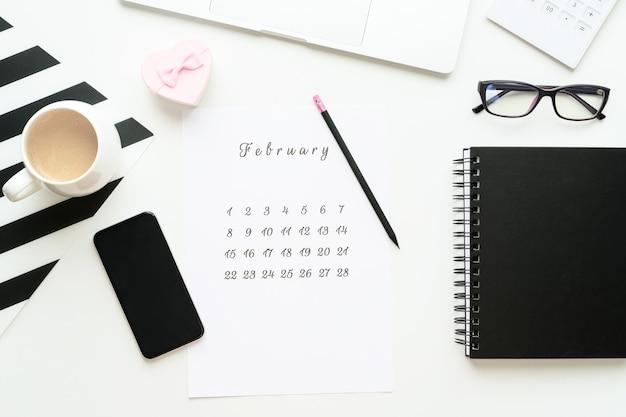 14. februar kalender auf arbeitsbereich mit rosa geschenkherz valentinstagskarte, tasse kaffee, flatlay