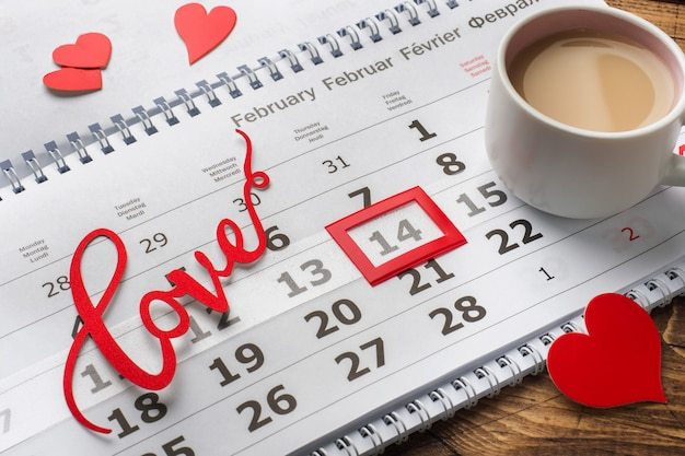 14. februar kalender. valentinstagkonzept, rote herzen, die wortliebe und ein tasse kaffee.