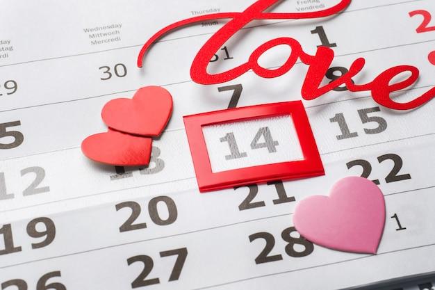 14. februar kalender. valentinstagkonzept, rote herzen und wortliebe