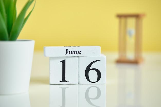 16 16. juni juni monatskalender konzept auf holzklötzen.
