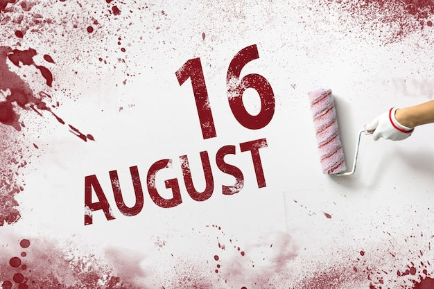16. august. tag 16 des monats, kalenderdatum. die hand hält eine rolle mit roter farbe und schreibt ein kalenderdatum auf einen weißen hintergrund. sommermonat, tag des jahreskonzepts.