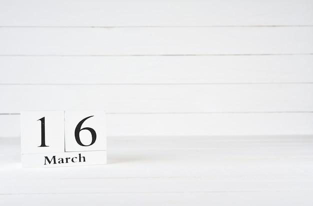 16. märz, tag 16 des monats, geburtstag, jahrestag, holzblockkalender auf weißem hölzernem hintergrund mit kopienraum für text.