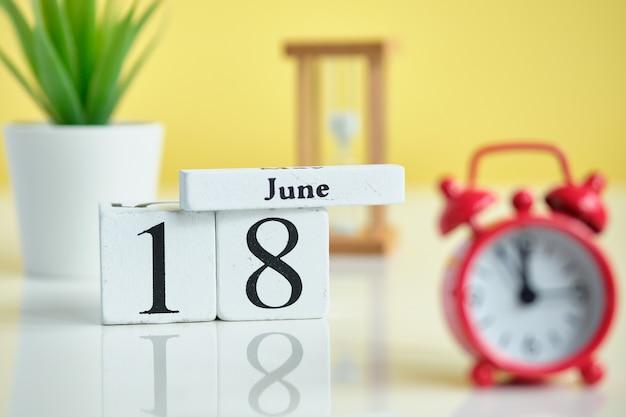 18 achtzehnten tag juni monat kalender konzept auf holzblöcken.