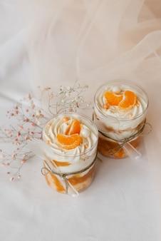 2 eiscreme in einer transparenten tasse mit mandarinen dekoriert