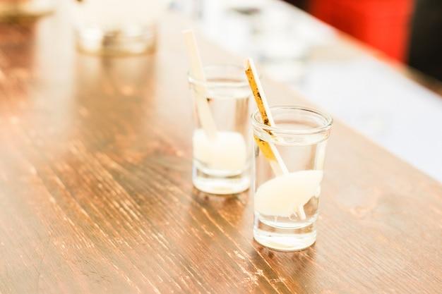 2 erfrischende schüsse alkohol auf holztisch
