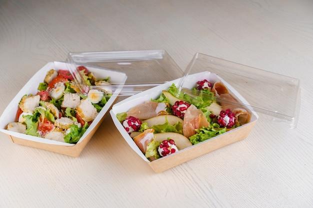 2 grüne natursalate in öko-thermobox mit microgreen, kalb, gurke, tomate, käse, granat, schale. sicherheitslieferung bei quarantäne covid 19.