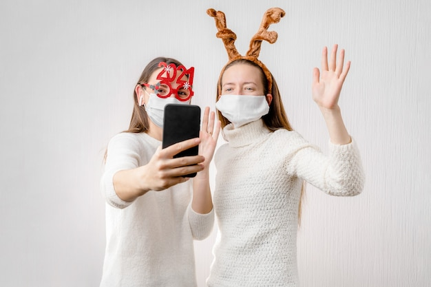 2 junge mädchen oder junge frau mit weihnachtsmütze und gesichtsmaske machen online-videoanruf. quarantäne