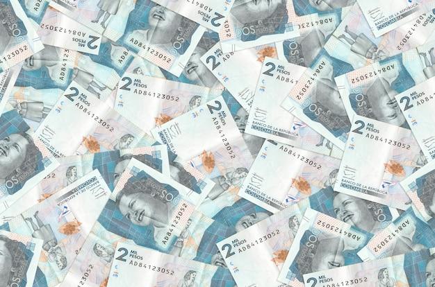 2 kolumbianische pesos-scheine liegen auf einem großen haufen. reichhaltige konzeptionelle wand des lebens. großer geldbetrag
