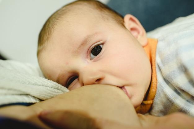 2 monate altes baby stillt die brust seiner mutter, das beste futter für einen säugling.