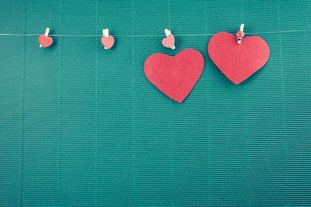 2 rote herzen und hangline mit grünem hintergrund, valentinsgrußkonzept