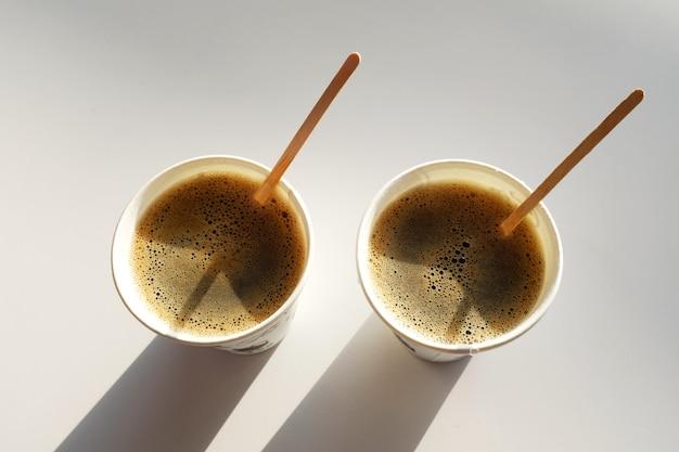 2 schachteln wegwerfpapierschalen ohne deckel auf dem tisch im café. kaffee zum mitnehmen. morgen. kaffee zum frühstück. 2 tassen kaffee. die schatten der tassen.