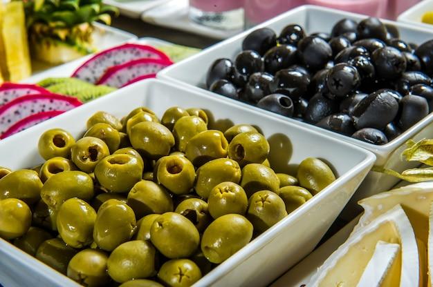 2 schalen mit olivensorte grüne oliven und schwarze oliven