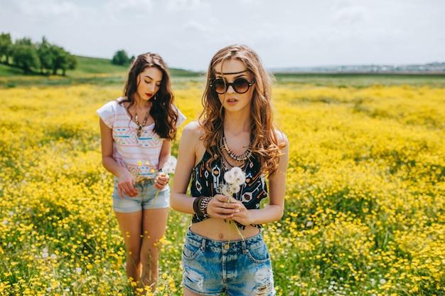 2 schönes hippiemädchen auf einem gebiet der gelben blumen