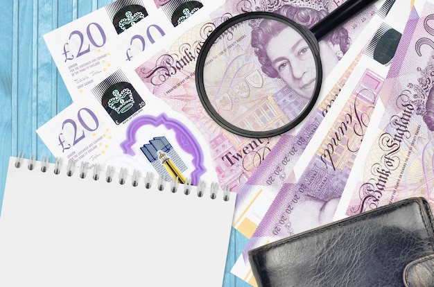 20 britische pfund scheine und lupe mit schwarzer geldbörse und notizblock