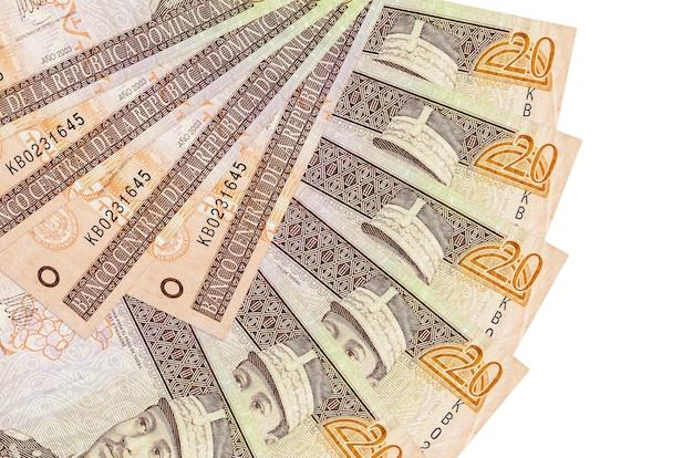 20 dominikanische peso-scheine liegen isoliert auf weißer wand mit in fächerform gestapeltem kopierraum in nahaufnahme. finanztransaktionskonzept
