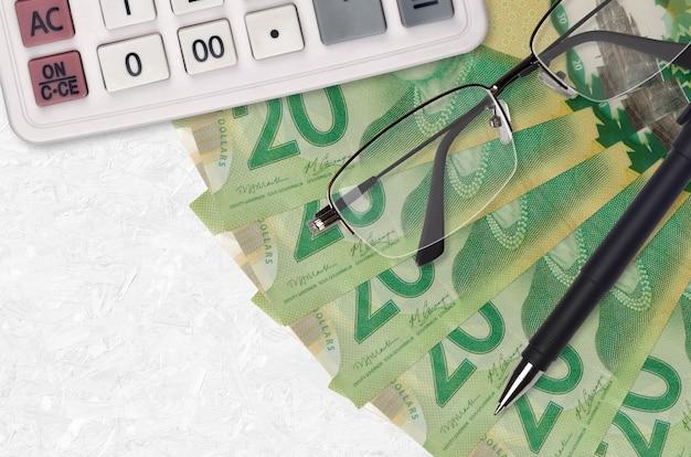 20 kanadische dollarnoten fan und taschenrechner mit brille und stift. geschäftskredit- oder steuerzahlungssaisonkonzept. finanzielle planung