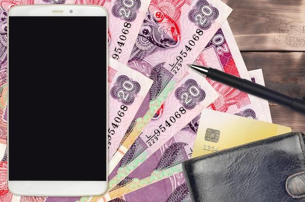20 srilankische rupien rechnungen und smartphone mit geldbörse und kreditkarte