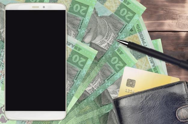 20 ukrainische griwna-rechnungen und smartphone mit geldbörse und kreditkarte