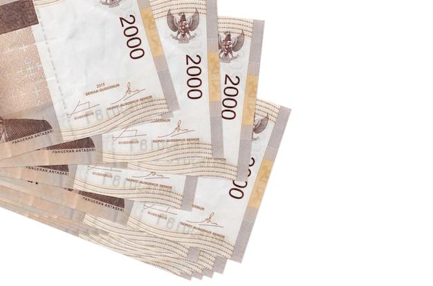 2000 indonesische rupiah-scheine liegen in kleinen bündeln oder packungen, die auf weiß isoliert sind. . geschäfts- und geldwechselkonzept