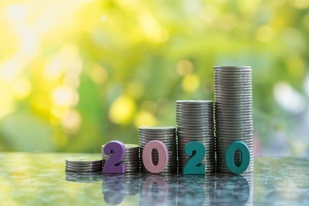 2010 neues jahr, geld und geschäftskonzept. schließen sie oben von der bunten zahl, die vor stapel silbermünzen mit grünem blattnaturhintergrund und kopienraum hölzern ist.