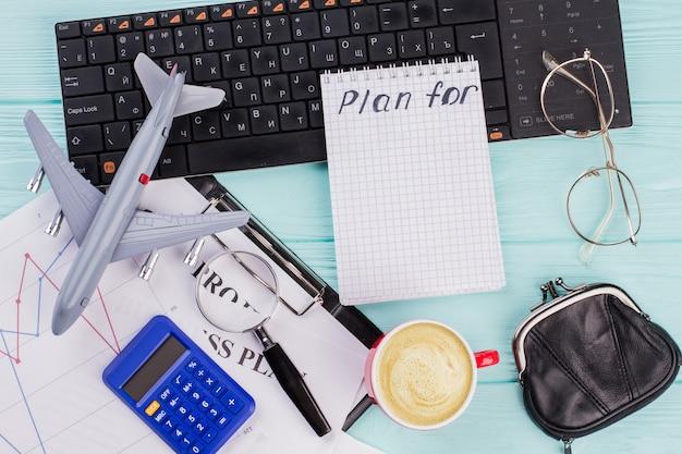 2018 pläne auf notebook mit reisezubehör brillengeldbörse und flugzeug auf holztischplatte hintergrund. reisen sie neues jahr urlaub urlaub konzept.