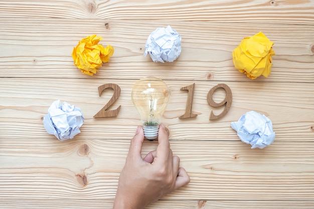 2019 glückliche neue jahre mit dem geschäftsmann, der glühlampe hält