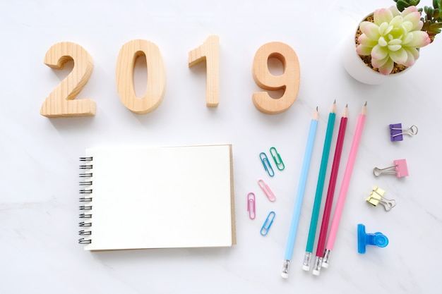 2019 hölzerne buchstaben, leeres notizpapier und verzierung auf weißem hölzernem hintergrund