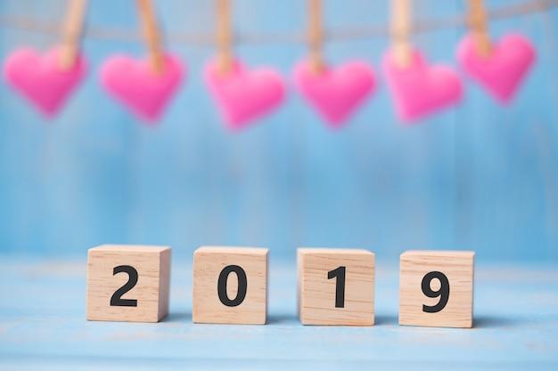 2019 hölzerne würfel mit rosa herzformdekoration auf blauem tabellenhintergrund und kopienraum für text. business, vorsatz, neujahr neues you und happy valentine's urlaubskonzept