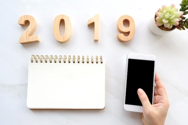 2019 holzbuchstaben, hand, die intelligentes telefon mit leerem bildschirm und leeres notizbuchpapier hält