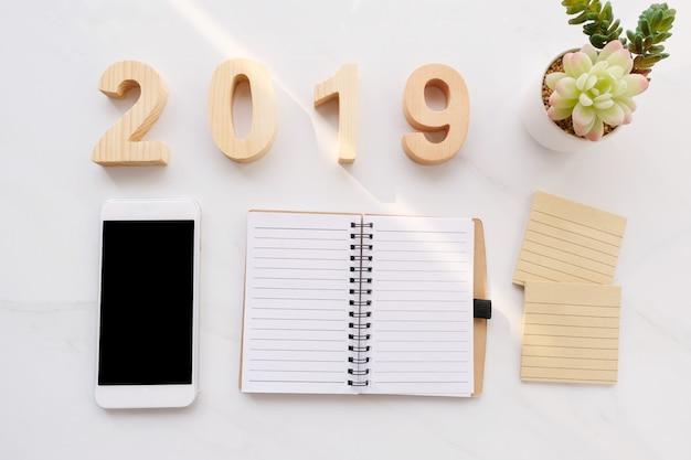 2019 holzbuchstaben, leeres notizbuchpapier, intelligentes telefon mit leerem bildschirm auf weißem marmor-bac