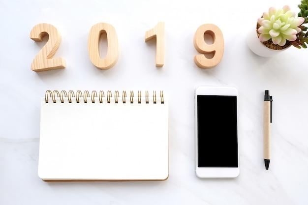 2019 holzbuchstaben, leeres notizbuchpapier, smartphone mit leerem bildschirm