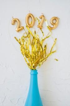 2019 inschrift aus kerzen mit lametta und flasche