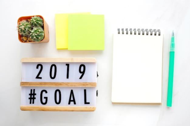 2019 ziele auf hölzernem kasten und leerem notizbuchpapier auf weißem marmorhintergrund