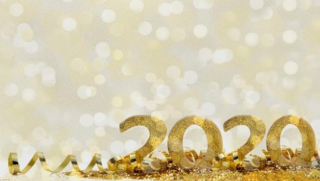 2020 goldene zahlen im funkeln und im band auf abstraktem unschärfenlichthintergrund