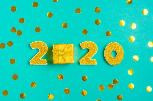 2020 goldene zahlen mit goldschimmer verziert, geschenkbox auf glänzend grüner minze.