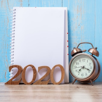 2020 guten rutsch ins neue jahr mit leerem notizbuch, retro- wecker und hölzerner zahl.