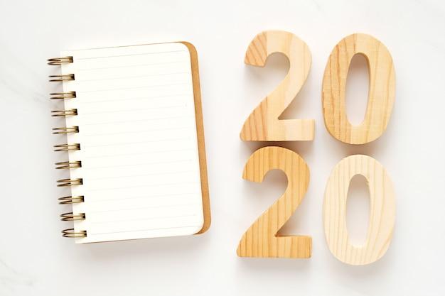 2020 hölzerne buchstaben und leeres notizbuchpapier auf weißem marmortabellenhintergrund