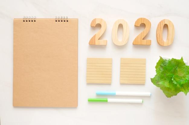 2020 hölzerne buchstaben und leeres notizbuchpapier mit kopienraum für hintergrund-fahnenkonzept des neuen jahres des textes