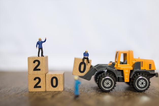 2020 neues jahr, arbeit und geschäftskonzept. schließen sie herauf gruppe arbeitskraftminiaturleute, die mit spielzeuglader-lkw-maschinenauto geladenem holzklotz der nr. 0 arbeiten, um block auf hölzerner tabelle zu stapeln und raum zu kopieren