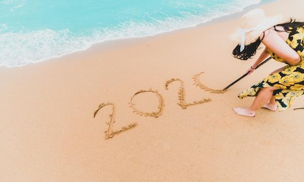 2020 neues jahr. frau 2020 geschrieben auf sandigen strand mit wellenschaum am seestrand. frohes neues jahr. tropische feier. neue jahre.