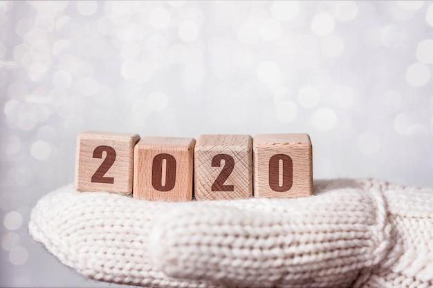 2020 neues jahr und weihnachten mit hölzernen würfeln auf wollhandschuhen