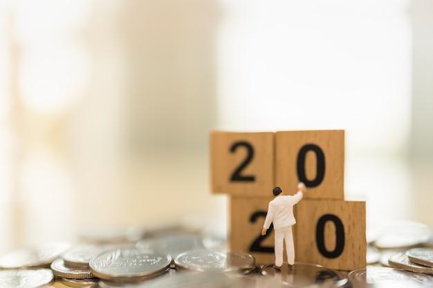 2020 neujahr, geschäfts-, spar- und planungskonzept. nahaufnahme des arbeiters miniaturfigur, die hölzernes zahlenblockspielzeug auf stapel von münzen mit kopienraum malt und reinigt.