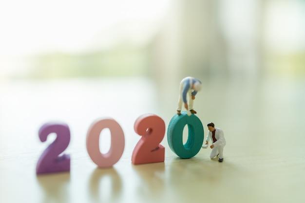 2020 neujahr, geschäfts- und planungskonzept. schließen sie oben von der gruppe der arbeiter-miniaturfigur, die bunte hölzerne zahl mit kopienraum malt und reinigt