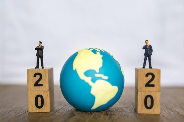 2020 neujahr, global- und business-konzept. schließen sie herauf zwei geschäftsmann-miniaturfigurmenschen, die auf stapel des hölzernen zahlenblocks und des mini-weltspielzeugballs mit kopienraum stehen