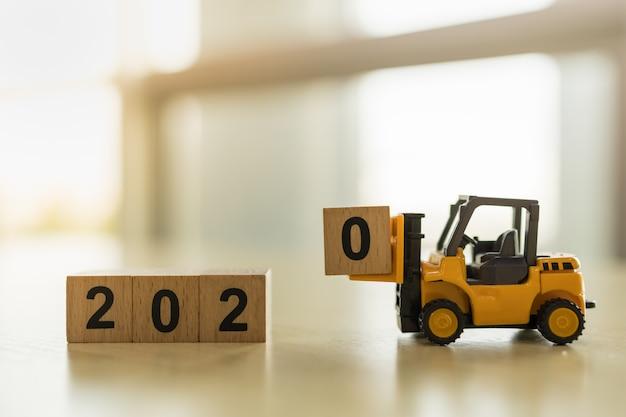 2020 neujahrskonzept. schließen sie oben vom geladenen holzklotzspielzeug der spielzeuggabelstapler-maschinenauto nr. 0 auf tabelle mit kopienraum