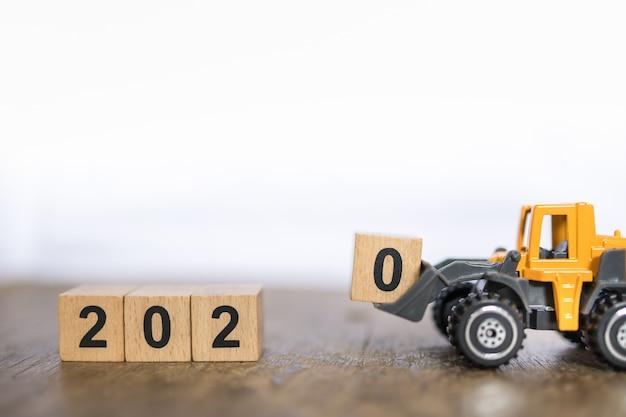 2020 neujahrskonzept. schließen sie oben von spielzeuglader-lkw-maschinenauto geladenem holzklotzspielzeug der nr. 0 auf hölzernem tabellen- und kopienraum