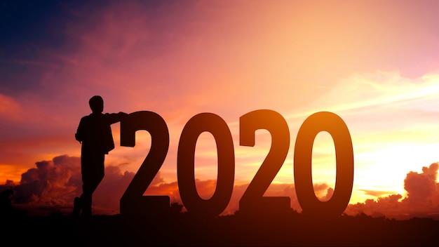 2020 silhouettieren sie jungen mann freiheit und guten rutsch ins neue jahr-konzept